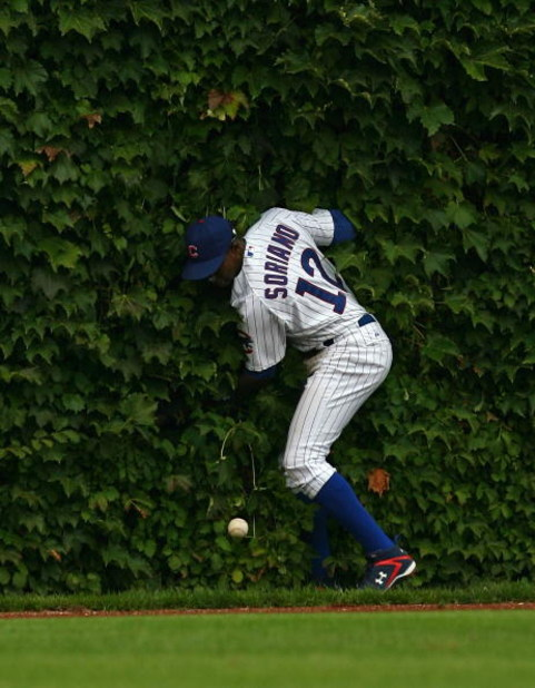 CHICAGO - AUGUST 28: Alfonso Soriano #12 of the Chicago Cubs hits the outfield wall after missing a catch against the New York Mets on August 28, 2009 at Wrigley Field in Chicago, Illinois. The Cubs defeated the Mets 5-2. (Photo by Jonathan Daniel/Getty I