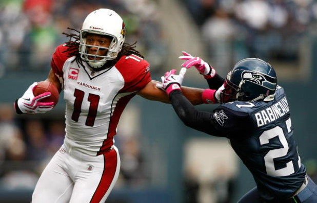 SEATTLE, WA - OCTOBER 18:  Larry Fitzgerald #11 of the Arizona Cardinals breaks a tackle by Jordan Babineaux #27 of the Seattle Seahawks at Qwest Field on October 18, 2009 in Seattle, Washington.  (Photo by Jonathan Ferrey/Getty Images)