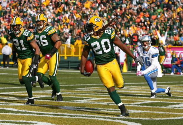 GREEN BAY, WI - OCTOBER 18: Atari Bigby #20 of the Green Bay Packers celebrates an interception in the end zone on a pass intended for John Standeford #16 of the Detroit Lions as teammates Charles Woodson #21 and Nick Barnett#56 run off the field at Lambe