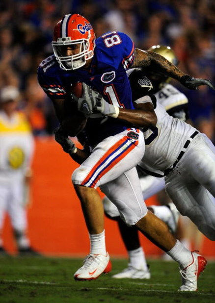 GAINESVILLE, FL - SEPTEMBER 5:  Aaron Hernandez #81 of the Florida Gators runs for a touchdown over Fred Godfrey #46 of the Charleston Southern Buccaneers during the game at Ben Hill Griffin Stadium on September 5, 2009 in Gainesville, Florida.  (Photo by