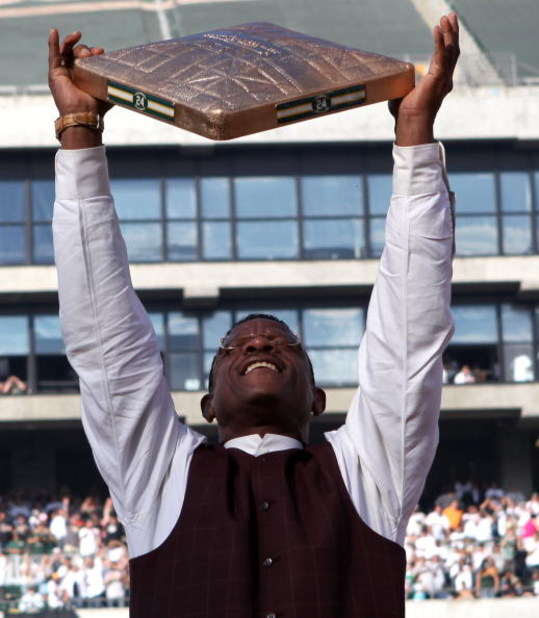 OAKLAND, CA - AUGUST 01:  Hall of Fame baseball player Rickey Henderson holds up a golden base during a ceremony to retire his number 24 by the Oakland Athletics before the start of the game against the Toronto Blue Jays August 1, 2009 at the McAfee Colis