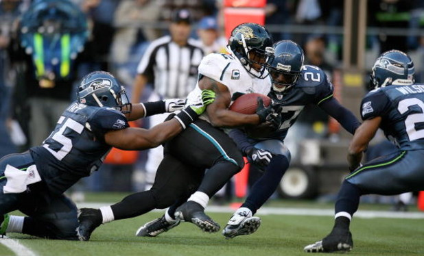 SEATTLE - OCTOBER 11:  Running back Maurice Jones-Drew #32 of the Jacksonville Jaguars rushes against Darryl Tapp #55 and Jordan Babineaux #27 of the Seattle Seahawks on October 11, 2009 at Qwest Field in Seattle, Washington. The Seahawks defeated the Jag