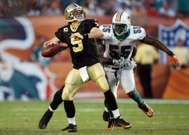 MIAMI - OCTOBER 25:  Quarterback Drew Brees #9 of the New Orleans Saints throws a pass before being hit by linebacker Joey Porter #55 of the Miami Dolphins at Land Shark Stadium on October 25, 2009 in Miami, Florida. The Saints defeated the Dolphins 46-34