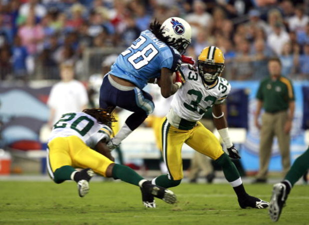 NASHVILLE, TN - SEPTEMBER 3: Chris Johnson #28 of the Tennessee Titans attempts to jump over defenders Atari Bigby #20 and Brandon Underwood #33 of the Green Bay Packers during a preseason NFL game at LP Field on September 3, 2009 in Nashville, Tennessee.