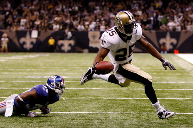 NEW ORLEANS - OCTOBER 18:  Reggie Bush #25 of the New Orleans Saints scores a touchdown over Kevin Dockery #35 of the New York Giants at the Louisiana Superdome on October 18, 2009 in New Orleans, Louisiana.  (Photo by Chris Graythen/Getty Images)