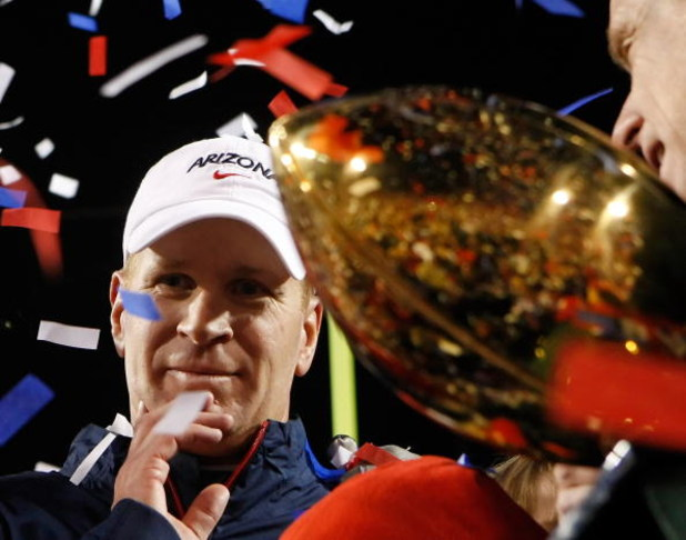 LAS VEGAS - DECEMBER 20:  Head coach Mike Stoops of the Arizona Wildcats is presented with a trophy after defeating the Brigham Young University Cougars 31-21 in the Pioneer Las Vegas Bowl at Sam Boyd Stadium December 20, 2008 in Las Vegas, Nevada.  (Phot