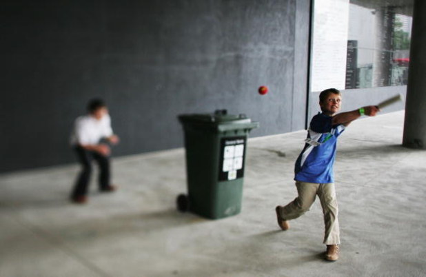 MELBOURNE, AUSTRALIA - DECEMBER 27: (THIS IMAGE WAS CREATED USING A VARIABLE PLANED LENS) Kids play cricket using a toy bat and a wheelie bin during the fourth Ashes test at the Melbourne Cricket Ground December 27, 2006 in Melbourne, Australia. The Ashes