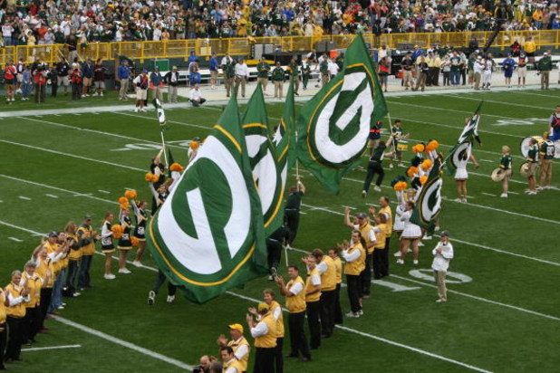 GREEN BAY, WI - SEPTEMBER 09: Cheerleaders carry flags of the Green Bay Packers as they run onto the field before a game against the Philadelphia Eagles on September 9, 2007 at Lambeau Field in Green Bay, Wisconsin. The Packers defeated the Eagles 16-13.