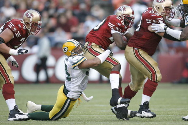 SAN FRANCISC0 - AUGUST 16:  Linebacker Brady Poppinga #51 of the Green Bay Packers drags down running back DeShaun Foster #29 of the San Francisco 49er during a preseason game at Candlestick Park on August 16, 2008 in San Francisco, California. San Franci