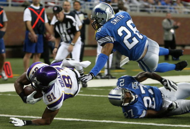 DETROIT - DECEMBER 07:  Tight end Visanthe Shiancoe #81 of the Minnesota Vikings scores a 11 yard touchdown reception past Dwight Smith #26 and Daniel Bullocks #17 of the Detroit Lions during the fourth quarter of the NFL game at Ford Field on December 7,