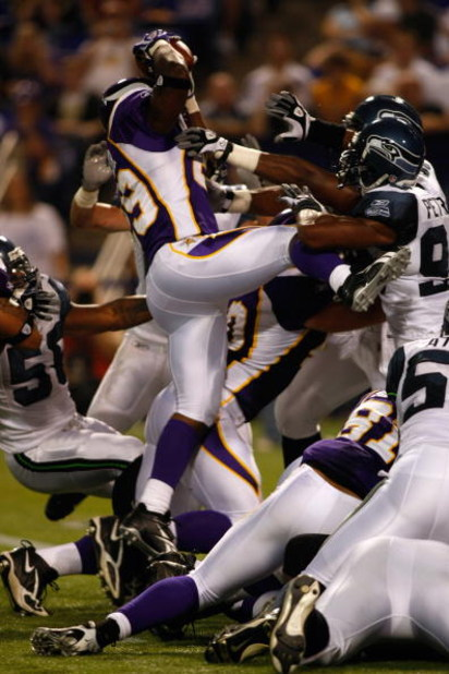 MINNEAPOLIS, MN - AUGUST 8: Running back Chester Taylor #29 of the Minnesota Vikings jumps in the air to score a touchdown as defenders try and hold him back against the Seattle Seahawks at the Hubert H. Humphrey Metrodome on August 8, 2008 in Minneapolis