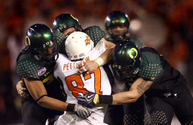 SAN DIEGO, CA - DECEMBER 30:   Tight End Brandon Pettigrew #87 of the Oklahoma State University Cowboys is tackled by the defense of the University of Oregon Ducks during the Ducks 42-31 win over the Cowboys in the Pacific Life Holiday Bowl at Qualcomm St