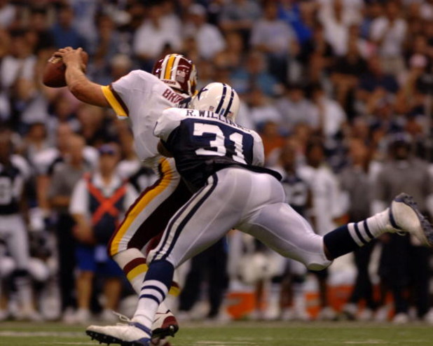 Washington Redskins  quarterback Mark Brunell scrambles from the pass rush  by  Dallas Cowboys safety Roy Williams  during a Monday Night Football game September 19, 2005 in Irving, Texas.  The Skins defeated the Cowboys 14 - 13.  (Photo by Al Messerschmi