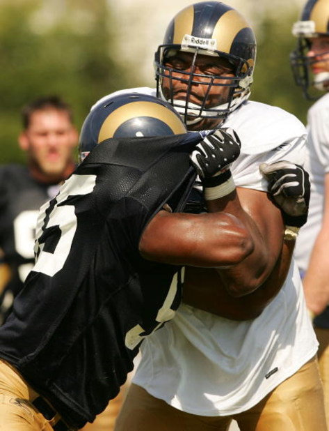 EARTH CITY, MO - JULY 29:  Orlando Pace #76 of the St. Louis Rams shoves teammate Anthony Hargrove #95 in a drill during St. Louis Rams Training Camp July 29, 2005 at Rams Park in Earth City, Missouri.  (Photo by Elsa/Getty Images)
