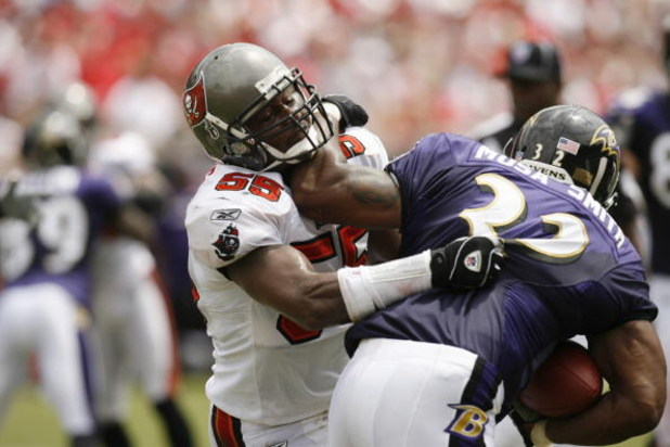 TAMPA, FL - SEPTEMBER 10:  Linebacker Derrick Brooks #55 of the Tampa Bay Buccaneers tries to stop running back Musa Smith #32 of the Baltimore Ravens during their NFL game on September 10, 2006 at Raymond James Stadium in Tampa, Florida. (Photo by Matt S