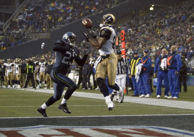 SEATTLE - NOVEMBER 13:  Marcus Trufant #23 of the Seattle Seahawks can't stop a touchdown pass to Torry Holt #81 of the St. Louis Rams during the game at Qwest Field on November 13, 2005 in Seattle, Washington.  The Seahawks won 31-16. (Photo by Otto Greu