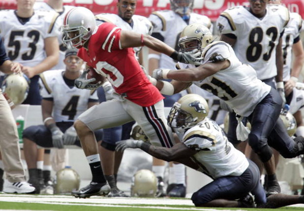 COLUMBUS - SEPTEMBER 8:  Brian Robiskie #80 of the Ohio State Buckeyes is forced out of bounds by Reggie Corner #20 and Andrew Johnson #21 of the Akron Zips in front of the Akron bench during the first quarter on September 8, 2007 at Ohio Stadium in Colum