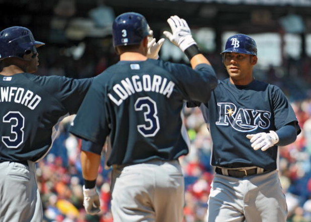PHILADELPHIA - APRIL 4: First baseman Carlos Pena #23 of the Tampa Bay Rays gets congratulated by teammates left fielder Carl Crawford #13 and third baseman Evan Longoria #3 after hitting a 3 run home-run in the top of the first inning during the game aga