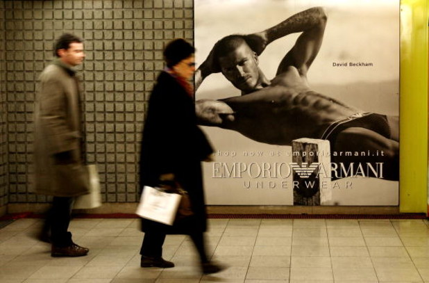MILAN, ITALY - DECEMBER 19:  People walking in the underground pass a poster featuring David Beckham modeling underwear in the latest Emporio Armani campaign on December 19, 2008 in Milan, Italy. It is anticipated that Victoria Beckham will accompany husb