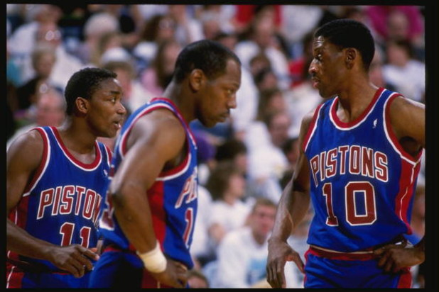 1988:  Guard Isiah Thomas, left, forward Dennis Rodman, right, and forward Vinnie Johnson of the Detroit Pistons talk to each other during a game. Mandatory Credit: Allsport  /Allsport