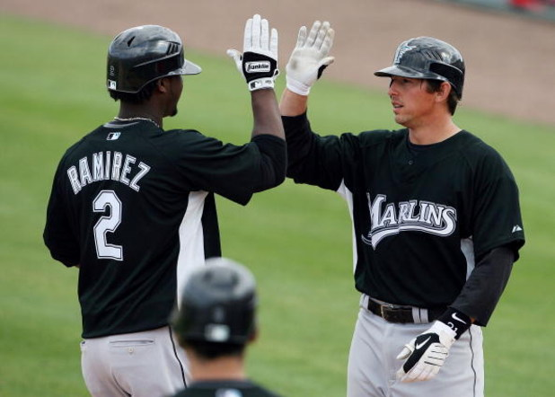 JUPITER, FL - FEBRUARY 25:  Hanley Ramirez #2 of the Florida Marlins is congratulated by John Baker #21 after driving home Baker with a two run home run in the sixth inning against the St. Louis Cardinals during a spring training game at Roger Dean Stadiu
