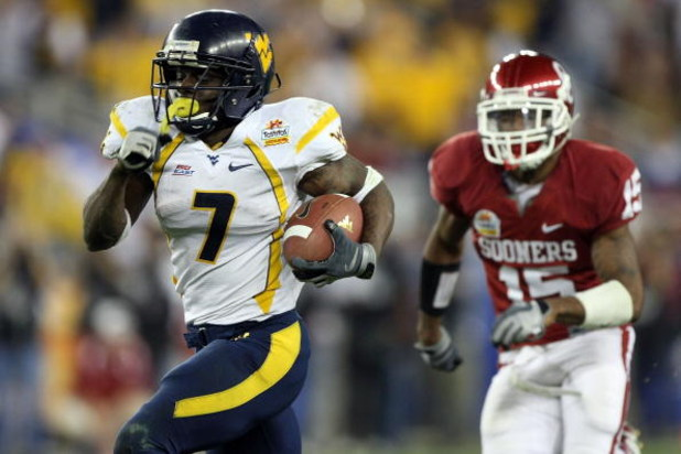 GLENDALE, AZ - JANUARY 02:  Running back Noel Devine #7 of the West Virginia Mountaineers runs for a 65-yard touchdown past Dominique Franks #15 of the Oklahoma Sooners in the second half at the Tostito's Fiesta Bowl at University of Phoenix Stadium Janua