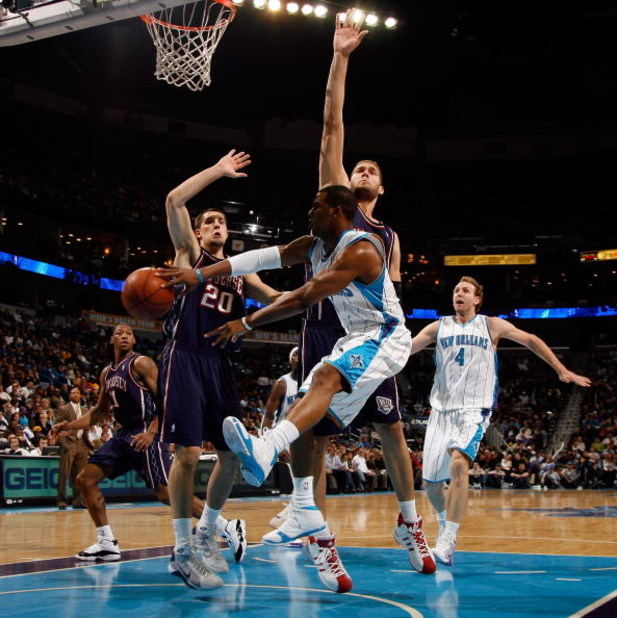 NEW ORLEANS - JANUARY 21:  Chris Paul #3 of the New Orleans Hornets passes the ball around Brook Lopez #11 of the New Jersey Nets on January 21, 2009 at the New Orleans Arena in New Orleans, Louisiana.  NOTE TO USER: User expressly acknowledges and agrees