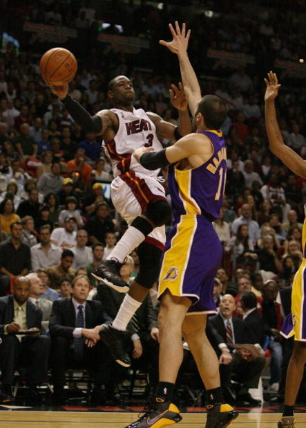 MIAMI - DECEMBER 19:  Dwyane Wade #3 of the Miami Heat passes around the defense of Vladimir Radmanovic #10 of the Los Angeles Lakers at American Airlines Arena on December 19, 2008 in Miami, Florida. The Heat defeated the Lakers 89-87. NOTE TO USER: User