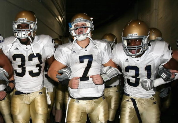 LOS ANGELES, CA - NOVEMBER 29:  Quarterback Jimmy Clausen #7 of the Notre Dame Fighting Irish walks out with teammates Robert Hughes #33 and Sergio Brown #31 before the game against the USC Trojans at Los Angeles Memorial Coliseum on November 29, 2008 in