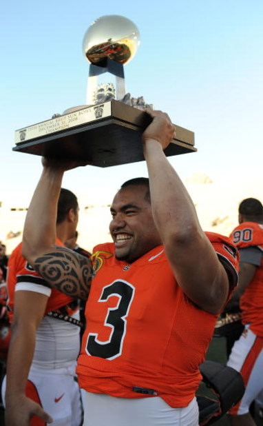 EL PASO, TX - DECEMBER 31:  Quarterback Lyle Moevao #3 of the Oregon State Beavers lifts the Sun Bowl trophy after a 3-0 win against the Pittsburgh Panthers during the Brut Sun Bowl at the Sun Bowl Stadium December 31, 2008 in El Paso, Texas.  (Photo by R