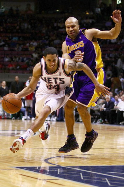 EAST RUTHERFORD, NJ - MARCH 27: Devin Harris #34 of the New Jersey Nets drives past Derek Fisher #2 of the Los Angeles Lakers during their game on March 27, 2009 at the Izod Center in East Rutherford, New Jersey. NOTE TO USER: User expressly acknowledges