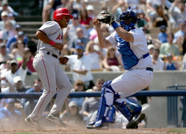 LOS ANGELES - APRIL 3:  Maicer Izturis #6 of the Los Angeles Angels of Anaheim is out at home plate by catcher Jason Phillips #17 of the Los Angeles Dodgers in the fifth inning of an exhibition game on April 3, 2004 at Dodger Stadium in Los Angeles, Calif