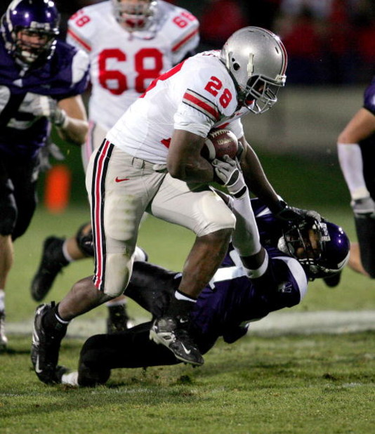 EVANSTON, IL - NOVEMBER 11:  Chris Wells #28 of the Ohio State Buckeyes carries the ball and stiff arms Reggie McPherson #27 of the Northwestern Wildcats on November 11, 2006 at Ryan Field in Evanston, Illinois. Ohio State defeated Northwestern 54-10.  (P
