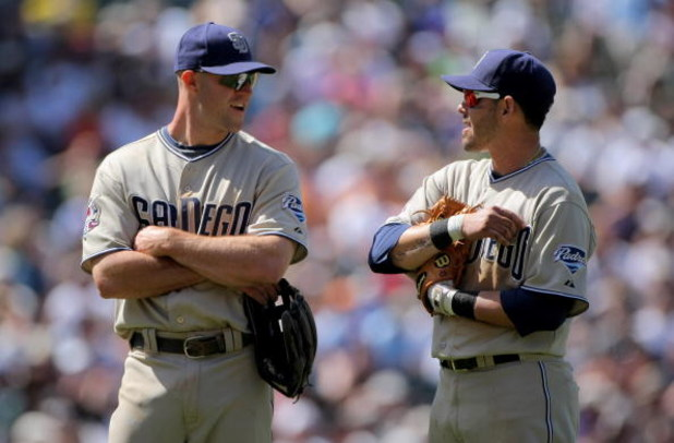 DENVER - APRIL 29:  Third baseman Kevin Kouzmanoff #5 and shortstop Luis Rodriguez #15 of the San Diego Padres await a pitching change against the Colorado Rockies during MLB action at Coors Field on April 29, 2009 in Denver, Colorado. The Rockies defeate