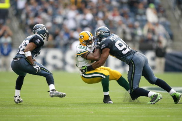 SEATTLE - OCTOBER 12:  Julian Peterson #98 of the Seattle Seahawks tackles DeShawn Wynn #42 of the Green Bay Packers during the game on October 12, 2008 at Qwest Field in Seattle, Washington. The Packers defeated the Seahawks 27-17. (Photo by Otto Greule