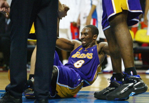 AUBURN HILLS, MI - JUNE 15:  Kobe Bryant #8 of the Los Angeles Lakers is helped up off the floor by teammate Shaquille O'Neal #34 (R) and a referee (L) after being fouled by the Detroit Pistons in the forth quarter of game five of the 2004 NBA Finals on J