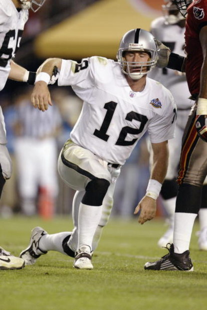 SAN DIEGO - JANUARY 26:  Quarterback Rich Gannon #12 of the Oakland Raiders gets picked up after being sacked for a one yard loss by Ellis Wyms #96 of the Tampa Bay Buccaneers at the Oakland 17 yardline at 4:41 of the third quarter of Super Bowl XXXVII on