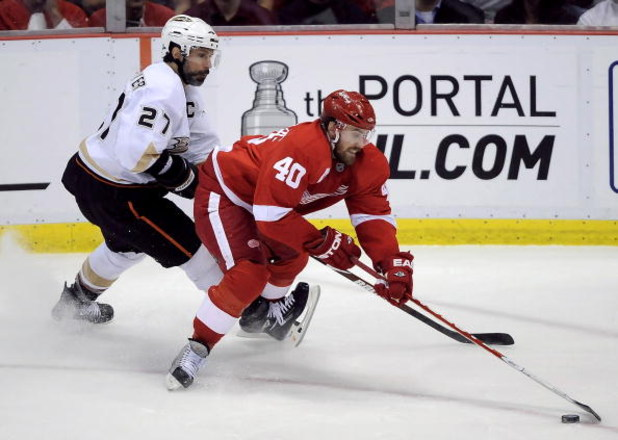 DETROIT - MAY 14:  Henrik Zetterberg #40 of the Detroit Red Wings tries to control the puck in front of Scott Niedermayer #27 of the Anaheim Ducks during Game Seven of the Western Conference Semifinals of the 2009 NHL Stanley Cup Playoffs on May 14, 2009