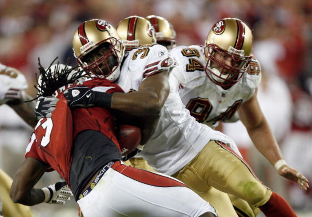 GLENDALE, AZ - NOVEMBER 10:  Michael Lewis #32 of the San Francisco 49ers makes a tackle on Tim Hightower #34 of the Arizona Cardinals during the fourth quarter at University of Phoenix Stadium on November, 10 2008 in Glendale, Arizona.  (Photo by Harry H