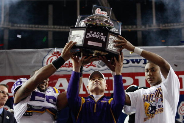 ATLANTA - DECEMBER 31: Linebacker Perry Riley #56, head coach Les Miles and quarterback Jordan Jefferson #9 of the LSU Tigers lift up the trophy after a 38-3 win over the Georgia Tech Yellow Jackets in the Chick-fil-A Bowl on December 31, 2008 at the Geor