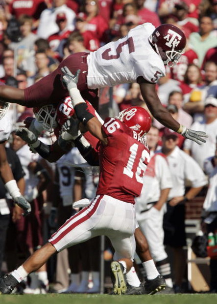 NORMAN, OK - NOVEMBER 12:  Defensive backs Chijioke Onyenegecha #22 and Lewis Baker #16 of the Oklahoma Sooners flip wide receiver Howard Morrow #5 of the Texas A&M Aggies as he runs to a first down in the second quarter on November 12, 2005 at Memorial S