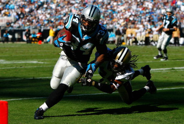 CHARLOTTE, NC - OCTOBER 19:  Running back DeAngelo Williams #34 of the Carolina Panthers rushes in for a touchdown past Mike McKenzie #34 of the New Orleans Saints during the game at Bank of America Stadium on October 19, 2008 in Charlotte, North Carolina
