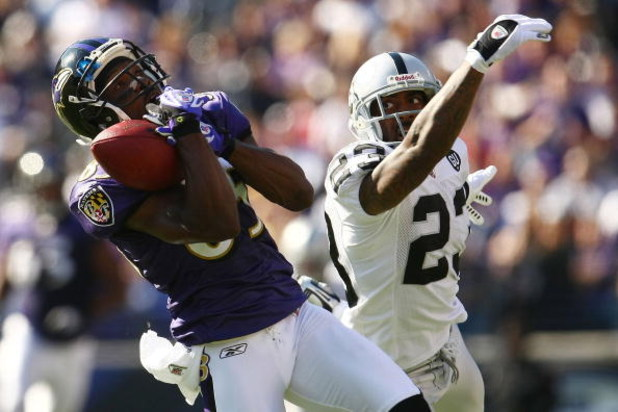 BALTIMORE - OCTOBER 26: Derrick Mason #85 of the Baltimore Ravens makes a catch under pressure from DeAngelo Hall #23 of the Oakland Raiders during the game at M&T Bank Stadium October 26, 2008 in Baltimore, Maryland.  (Photo by Chris McGrath/Getty Images
