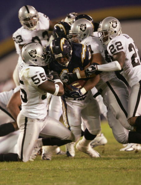 SAN DIEGO - DECEMBER 4:  Lorenzo Neal #41 of the San Diego Chargers grips the ball as he is tackled by Danny Clark #55 Renaldo Hill #22 of the Oakland Raiders on December 4, 2005 at Qualcomm Stadium in San Diego, California.  The Chargers won 34-10. (Phot