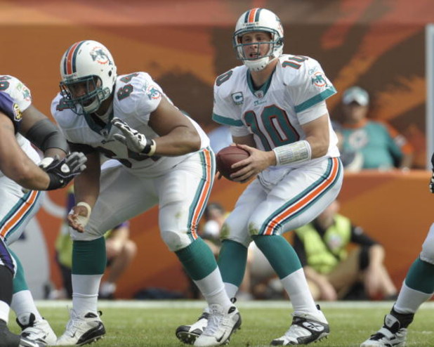 MIAMI, FL - JANUARY 4:  Quarterback Chad Pennington #10 of the Miami Dolphins takes a snap from center Samson Satele #64 against the Baltimore Ravens in an NFL Wildcard Playoff Game at Dolphins Stadium on January 4, 2009 in Miami, Florida.  (Photo by Al M