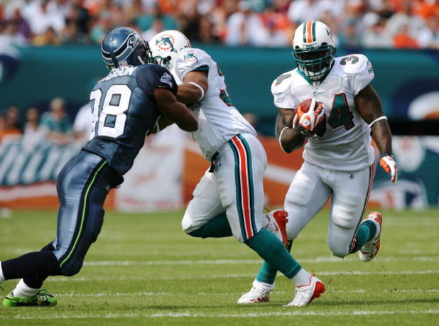MIAMI - NOVEMBER 09:  Running back Ricky Williams #34 of the Miami Dolphins looks for room to run as fullback Lousaka Polite #36 blocks linebacker Julian Peterson #98 of the Seattle Seahawks at Dolphin Stadium on November 9, 2008 in Miami, Florida. The Do