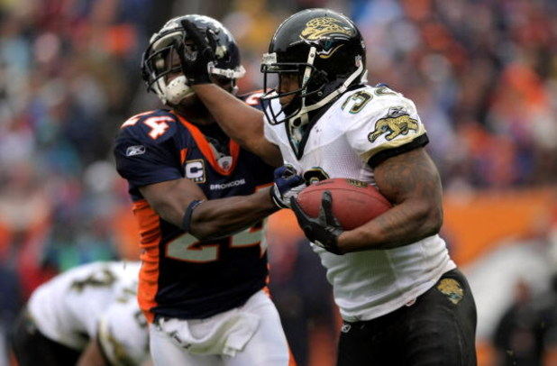 DENVER - OCTOBER 12:  Running back Maurice Jones-Drew #32 of the Jacksonville Jaguars runs the ball and tries to hold off cornerback Champ Bailey #24 of the Denver Broncos during NFL action at Invesco Field at Mile High on October 12, 2008 in Denver, Colo