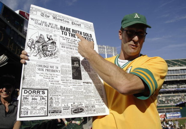 OAKLAND, CA - OCTOBER 6:  A fan of the Oakland A's holds up a replica of the January 6, 1920 edition of the Boston Post, when the Red Sox sold Babe Ruth to the New York Yankees that started the 'curse' in Game 5 of the 2003 American League Divisional Seri