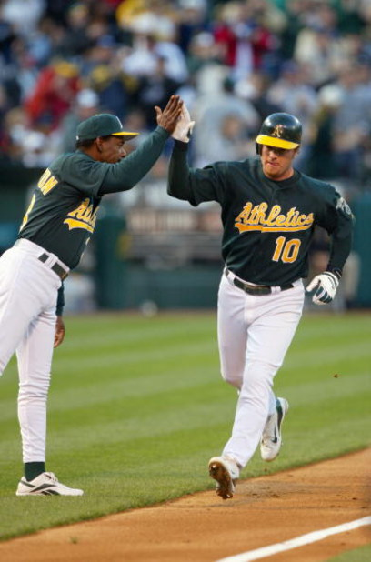 OAKLAND, CA - MAY 5:  Third base coach Ron Washington #10 of the Oakland Athletics high fives infielder Scott Hatteberg #10 after Hatterberg hit a home run against the New York Yankees during the game at Network Associates Coliseum on May 5, 2004 in Oakla