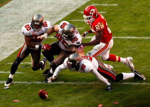 KANSAS CITY, MO - NOVEMBER 2:  Ronde Barber #20, Chris Hovan #95, and Tanard Jackson #36 of the Tampa Bay Buccaneers dive for a fumble by running back Jamaal Charles #25 of the Kansas City Chiefs during the game at Arrowhead Stadium November 2, 2008 in Ka